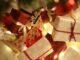 Gaver ligger i blandt lys ved juletræet