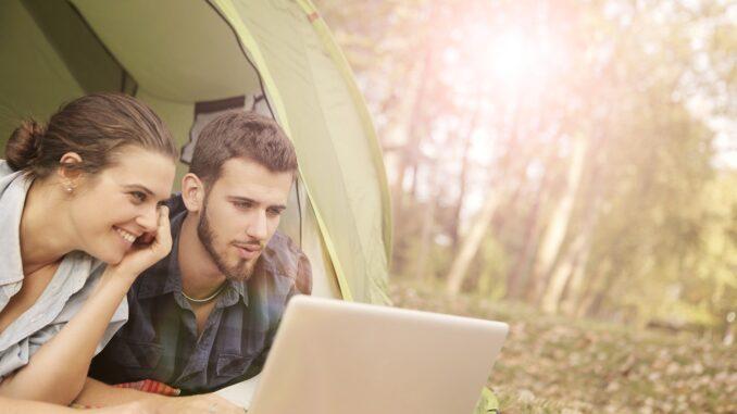 To personer kigger på computer i naturen